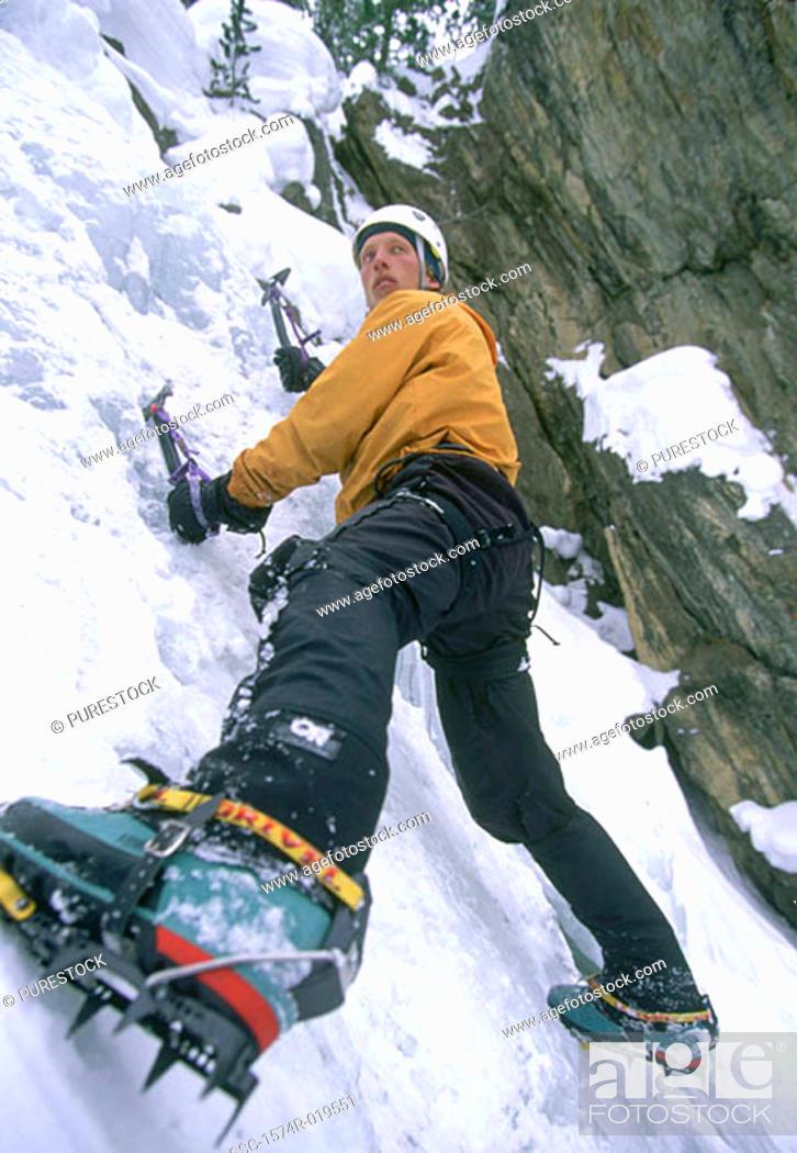 Stock Photo: Young adult man ice climbing, Utah, USA.