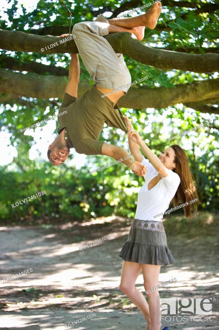 Stock Photo: A young man hanging from a tree, girlfriend pulling on his T-shirt.