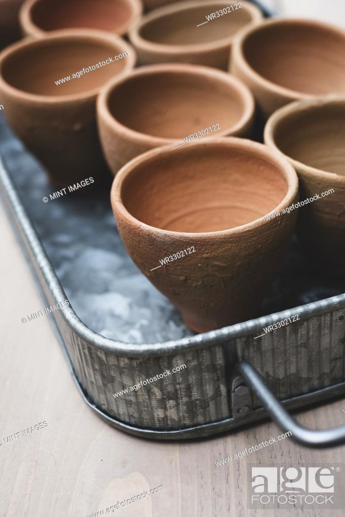 Stock Photo: High angle close up of terracotta plant pots on metal tray.