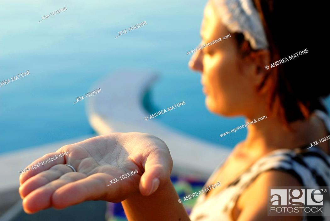 Stock Photo: A woman practicing a yoga position with open palm hand.