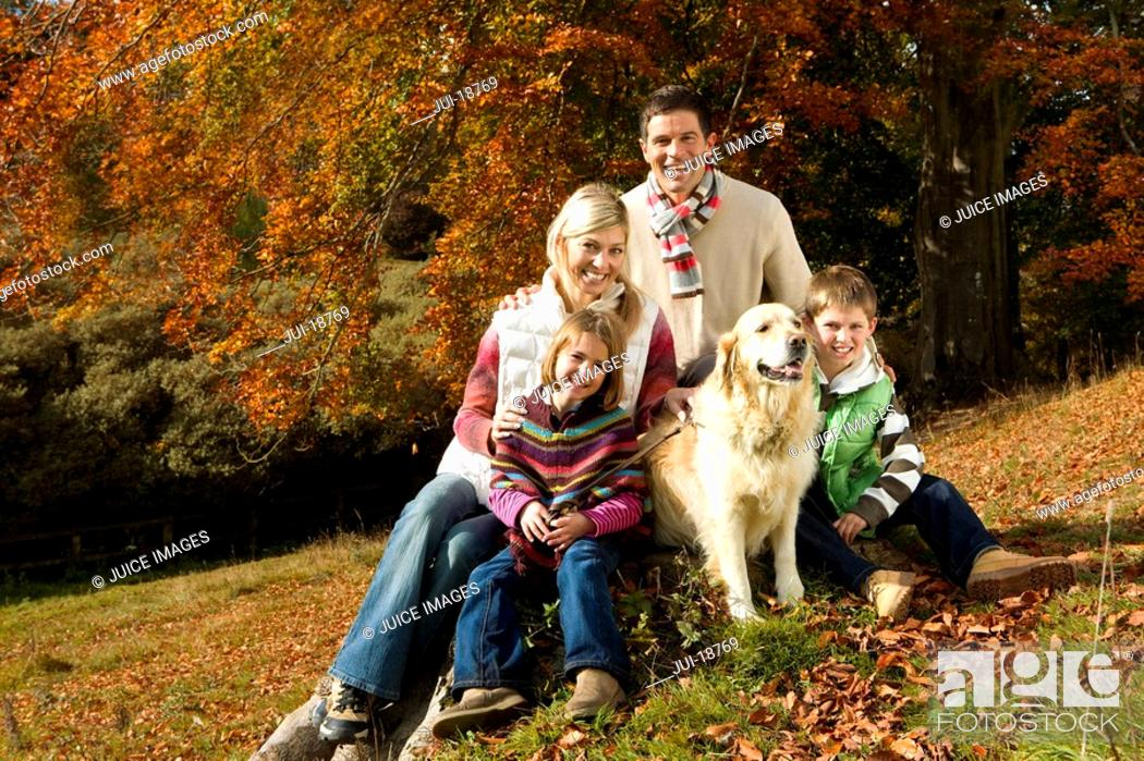Stock Photo: Family and dog sitting on tree stump in woods.