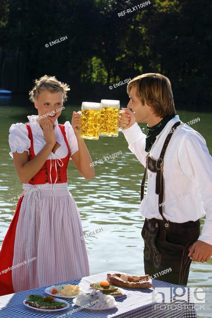 Stock Photo: Young couple in traditional Bavarian outfit, having meal in beer garden Munich.