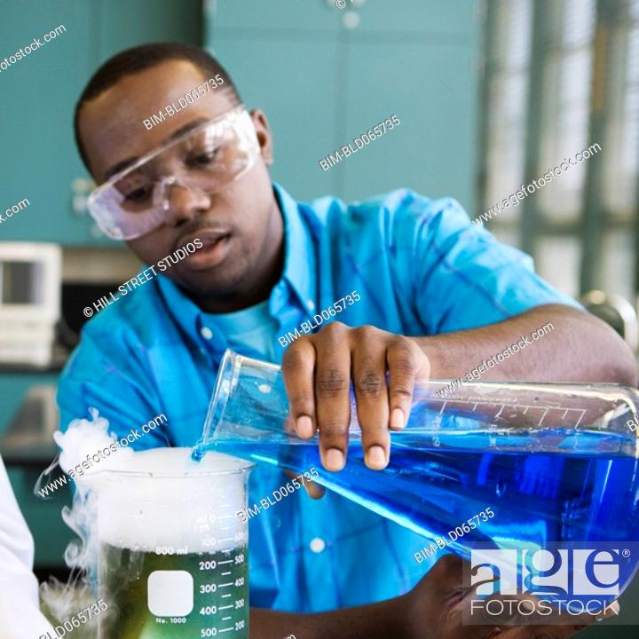 Stock Photo: African man performing experiment in chemistry lab.
