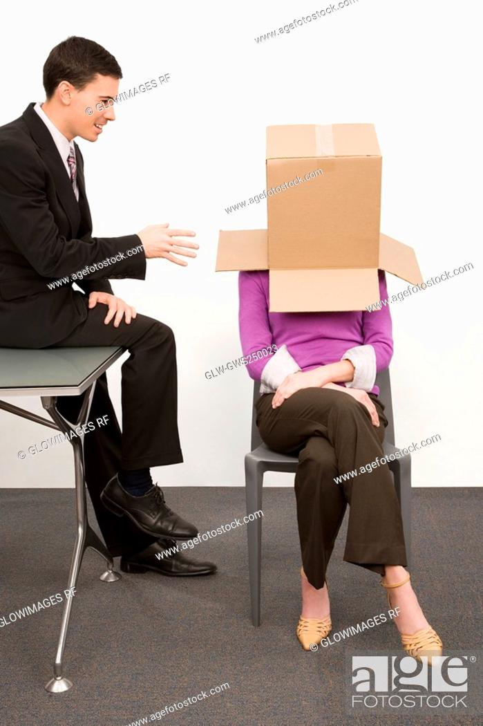 Stock Photo: Businesswoman covering her face with a cardboard box and a businessman sitting beside her on a desk.