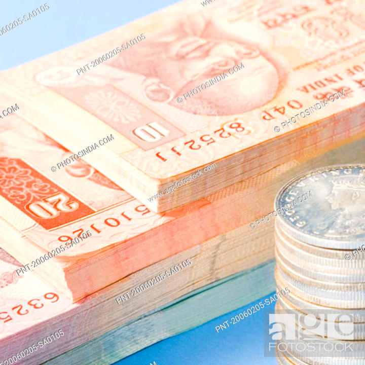 Stock Photo: Close-up of Indian banknotes with a stack of Indian silver coins.