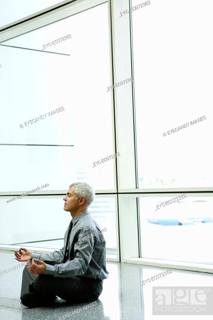 Stock Photo: Mature businessman doing yoga in airport.