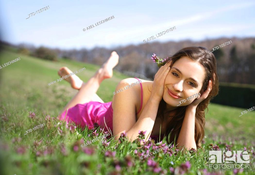 Stock Photo: Young brunette woman lying on a meadow grass landscape flowers lying nature park sun pink.