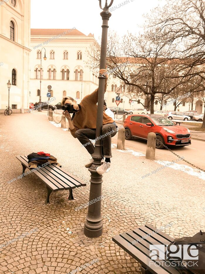 Imagen: playful photographer climbing on street lamp to photograph subject from above, at street in city Munich, Germany.