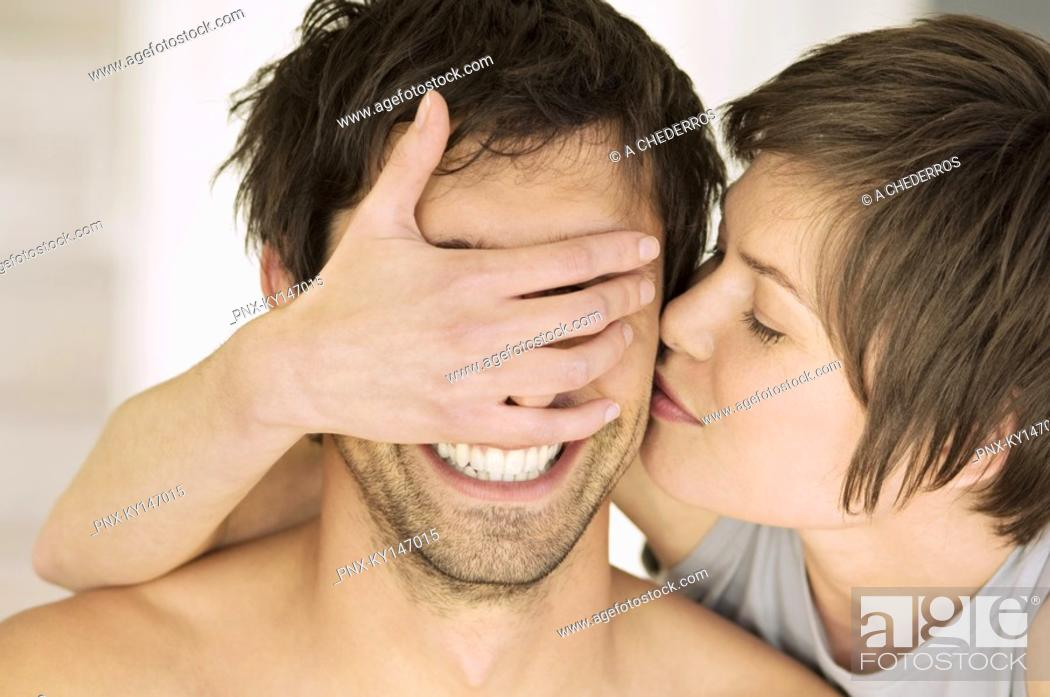 Stock Photo: Portrait of young woman kissing man, covering his eyes.