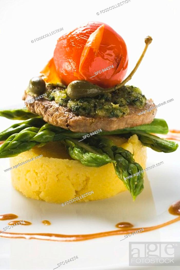 Stock Photo: Veal escalope with herb crust on polenta and asparagus.