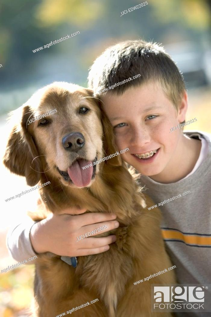 Imagen: Boy with braces smiling and hugging his dog.