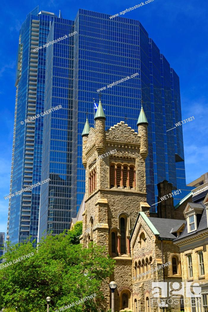 Stock Photo: Old St Andrews presbyterian church tower against modern blue glass highrise office tower Toronto.