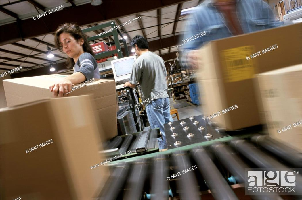 Stock Photo: Warehouse employees organizing cardboard boxes moving on a conveyor belt in a distribution warehouse.