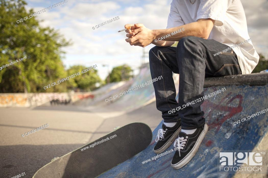 Stock Photo: Young rebellious man smoking cigarette with skateboard.