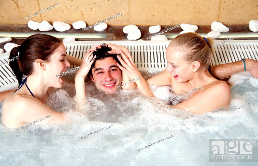 Stock Photo: One man with two women in jacuzzi at a spa.