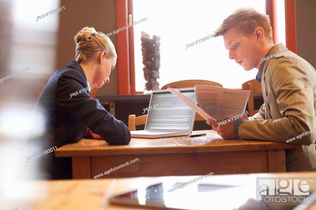 Stock Photo: Business couple sitting in a restaurant and working.
