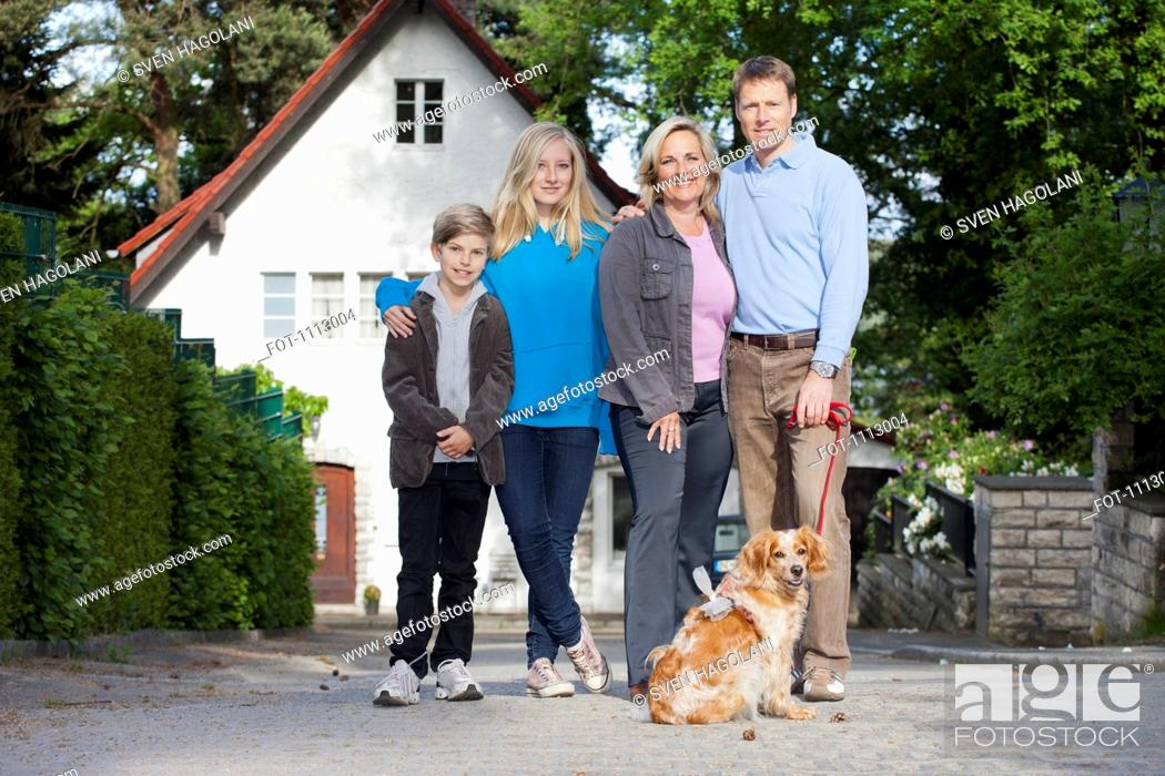 Stock Photo: A portrait of a family of four and their dog.