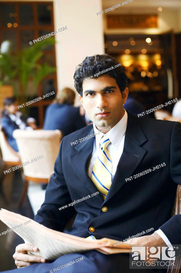 Stock Photo: Portrait of a businessman holding a newspaper.