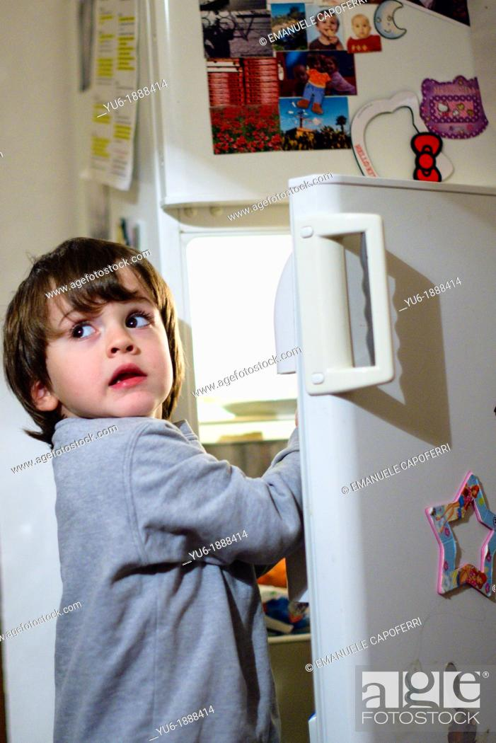 Stock Photo: Child in front of the fridge.