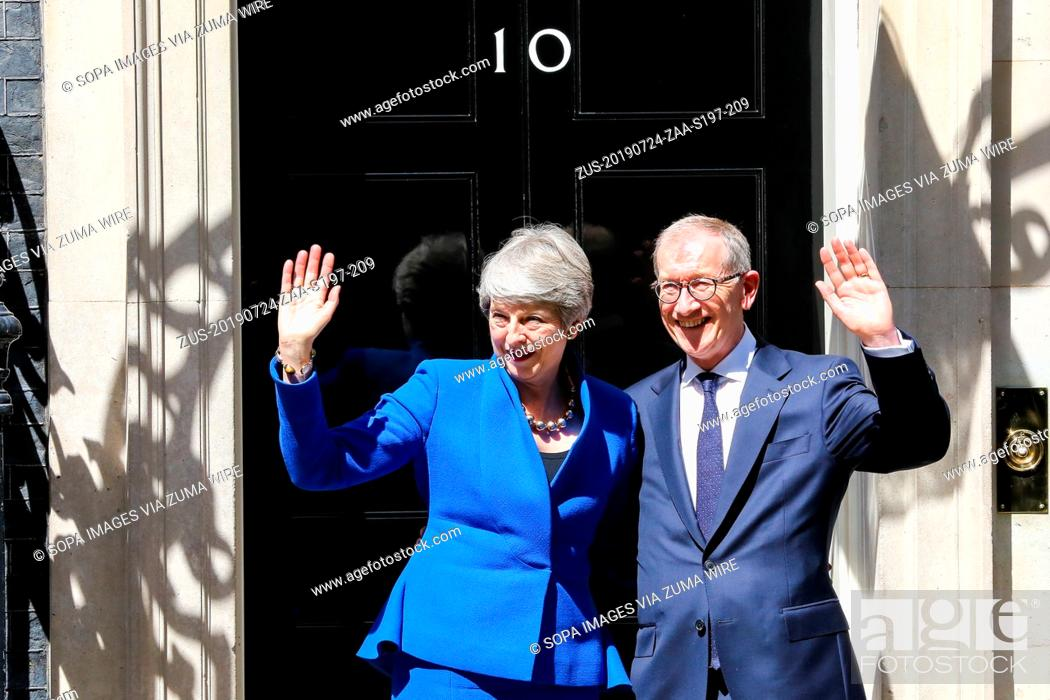 Stock Photo: July 24, 2019, London, United Kingdom: British Prime Minister Theresa May (L) and her husband Philip May (R) wave on the steps of 10 Downing Street after her.