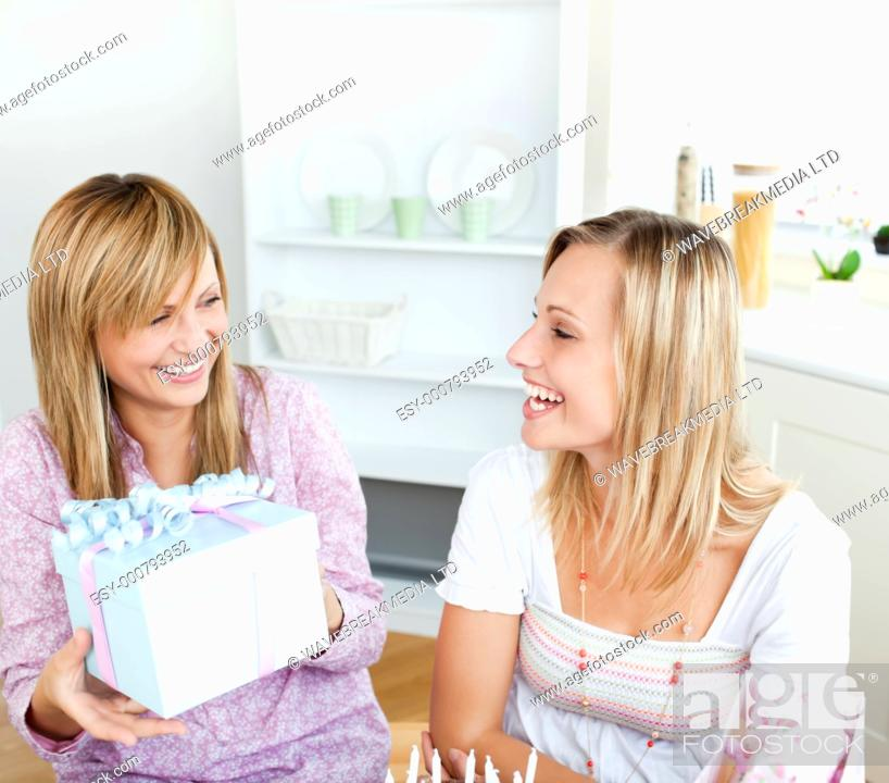 Stock Photo: Beautiful woman receiving a present during a birthday party with her friend at home.