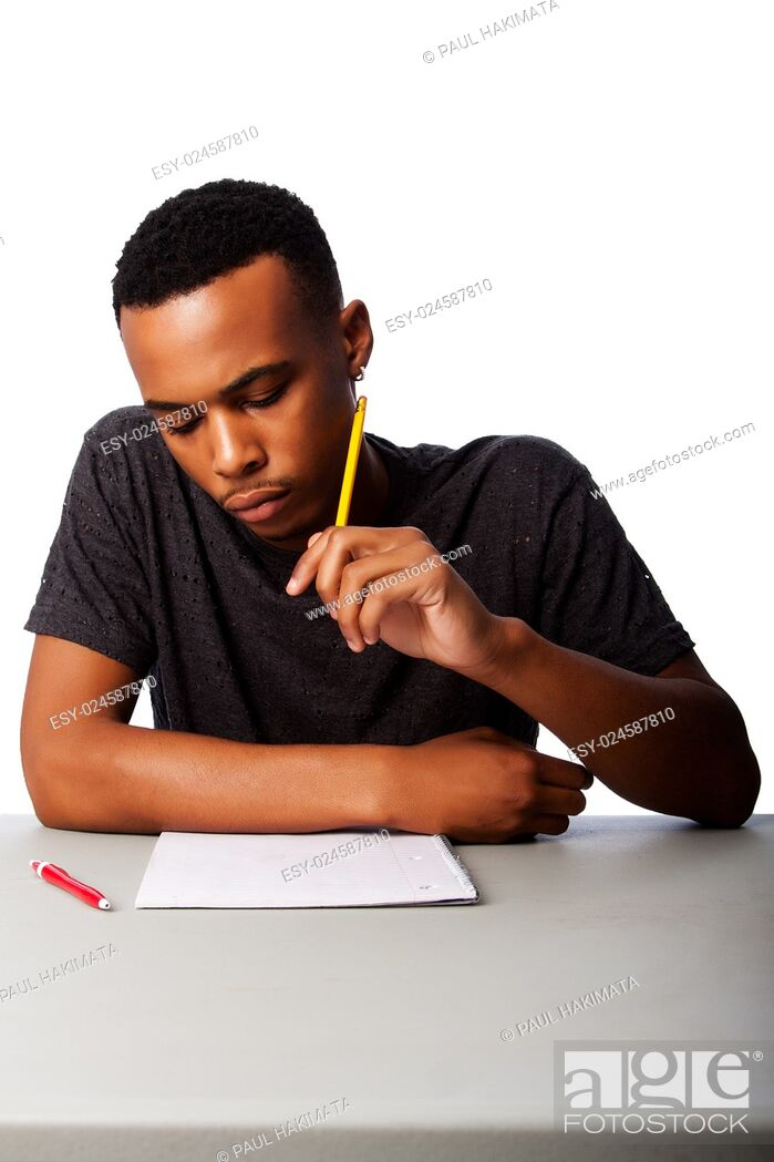 Stock Photo: Handsome student thinking concentrating focussing for test examination sitting at desk, on white.