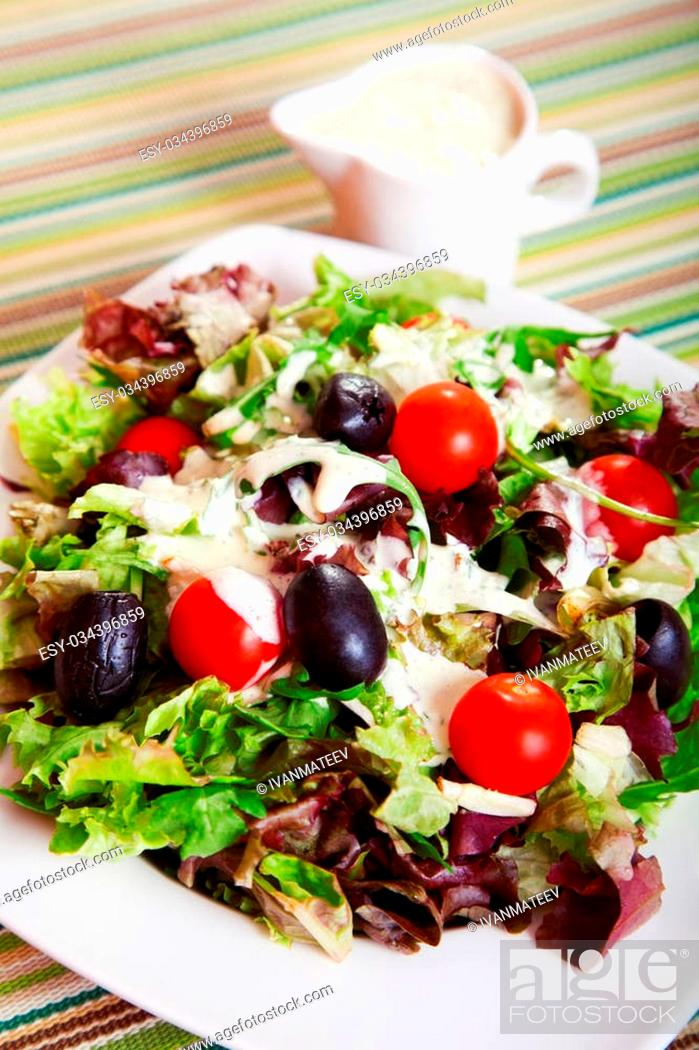 Stock Photo: Fresh salad with cherry tomatos, black olives and mayonnaise dressing.