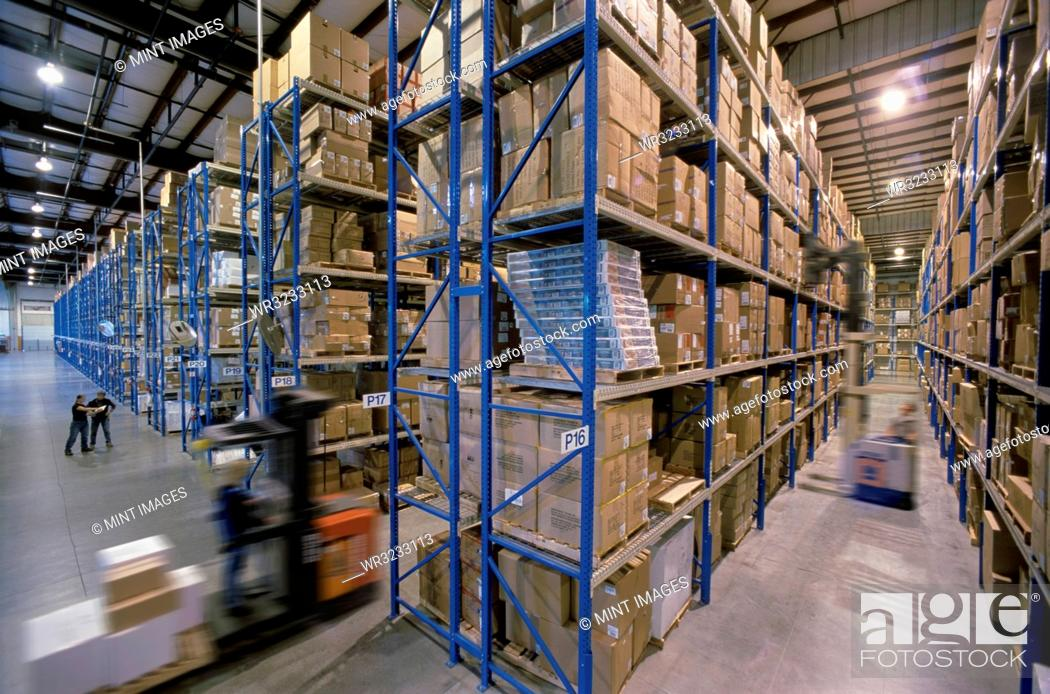 Stock Photo: Overview of a large industrial distribution warehouse storing products in cardboard boxes on conveyor belts and racks.