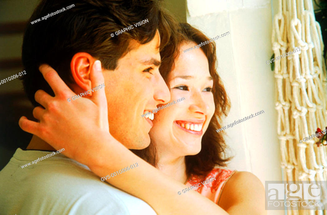 Stock Photo: Side profile of a young couple looking out a window.