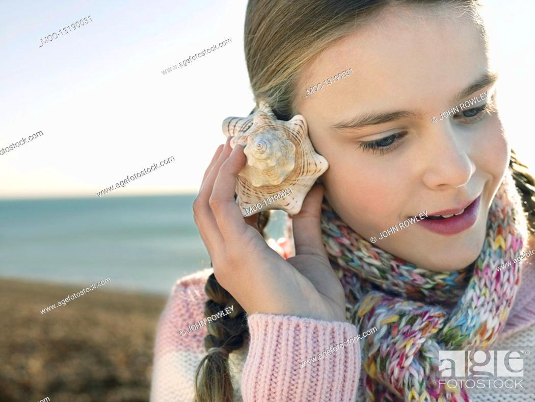 Stock Photo: Pre teen girl listening to seashell standing on beach close up.