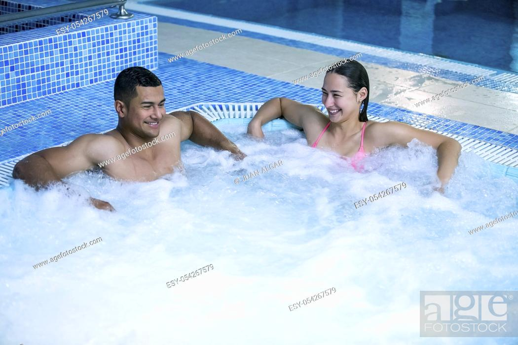 Stock Photo: Horizontal indoors shot of man and woman having fun and relaxing in swimming pool with bubbles.