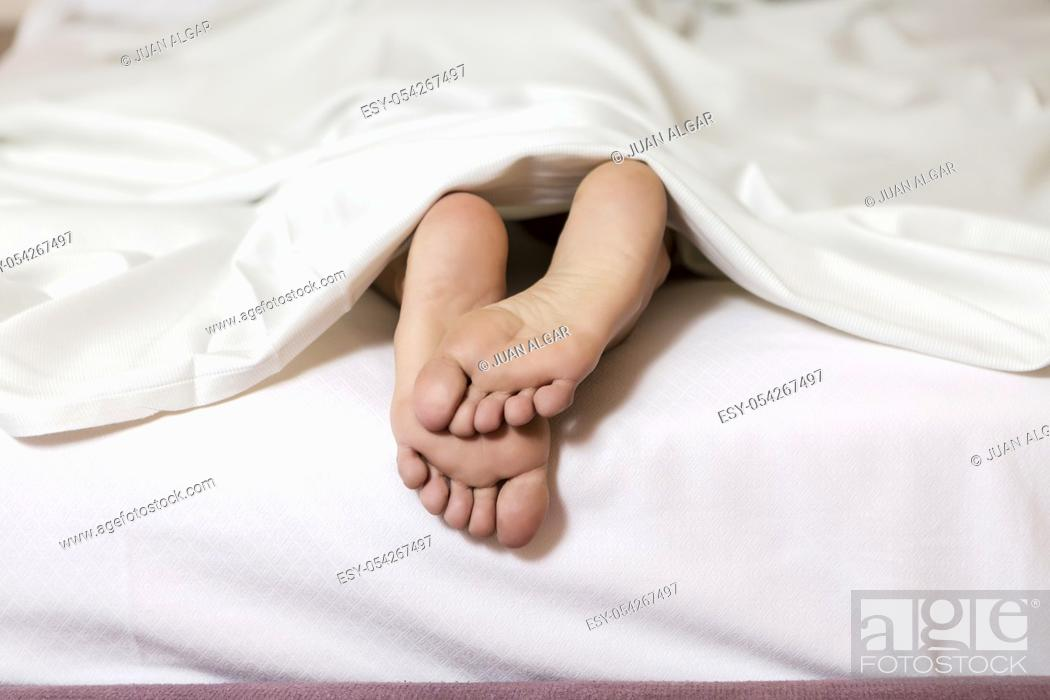 Stock Photo: Crop shot of female soft feet lying on white bed under blanket.