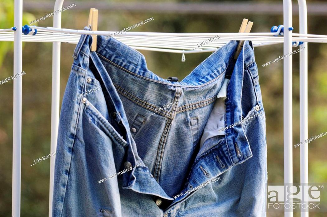 Stock Photo: Old, ripped, well worn jeans trousers put to dry.