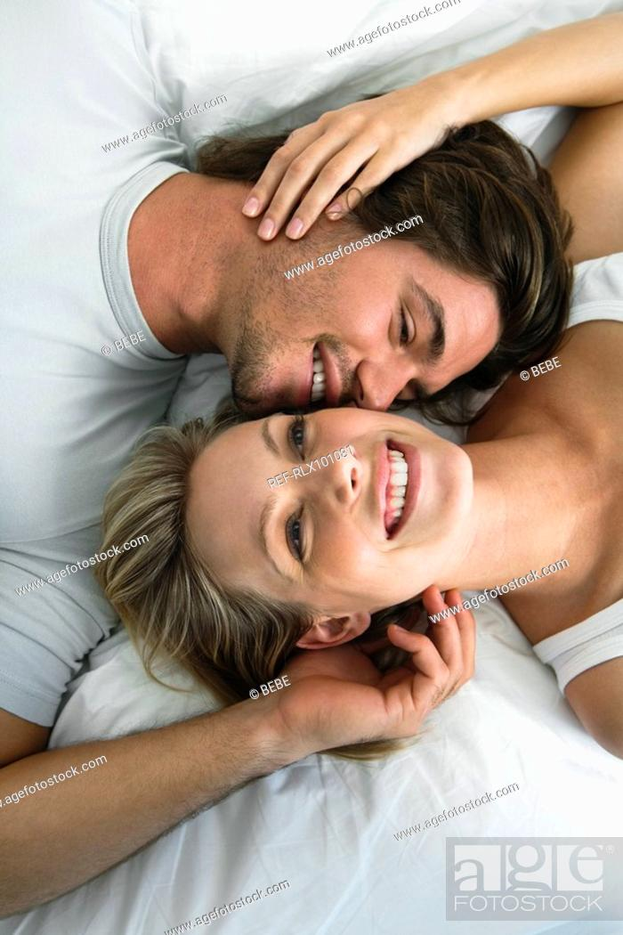 Stock Photo: Young couple lying in bed, smiling, portrait from above.