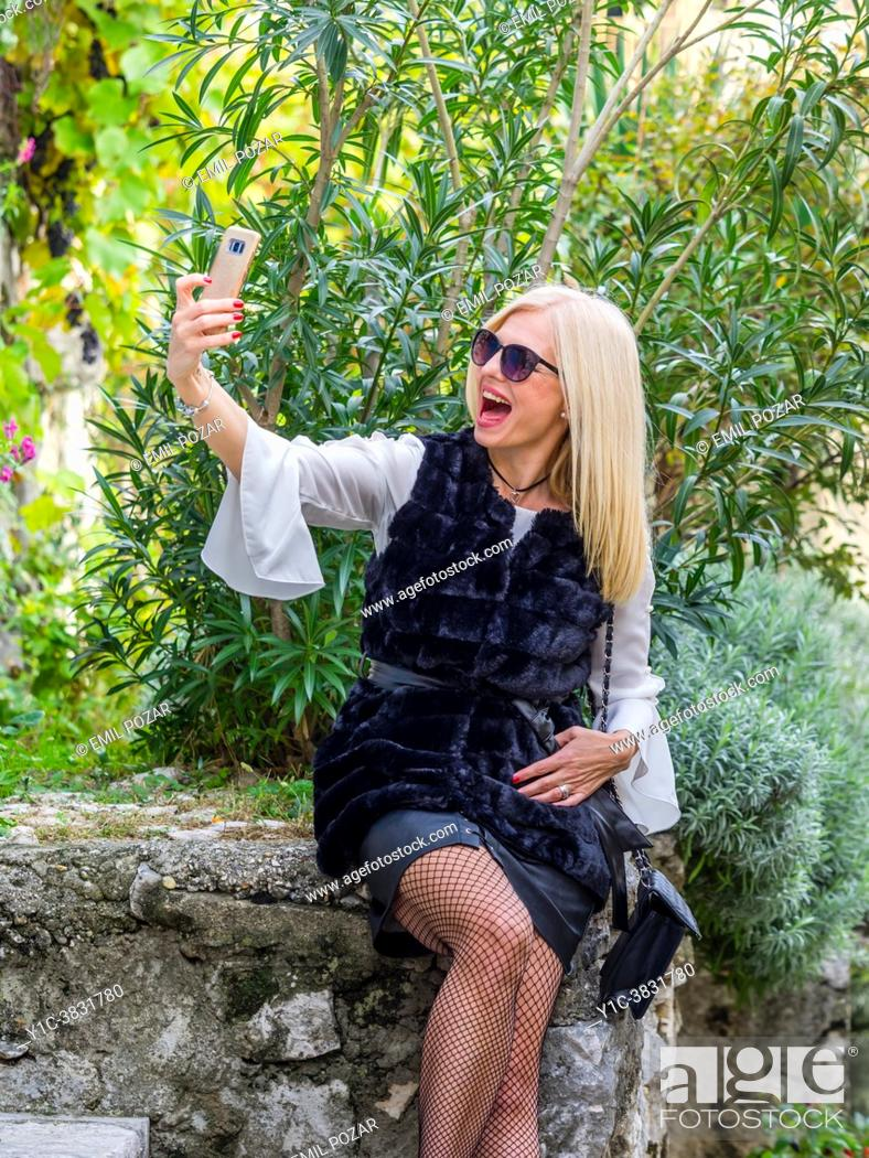 Stock Photo: Attractive mature blonde woman is taking selfie as she is positively surprised.