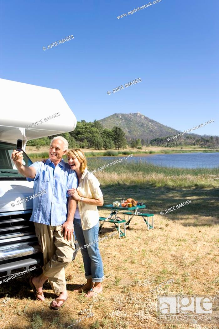 Stock Photo: Mature couple by lake and motor home taking photograph of themselves with mobile phone.