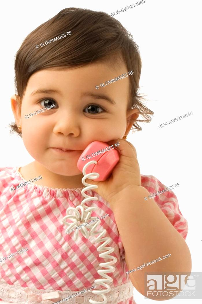 Stock Photo: Portrait of a girl using a toy phone.