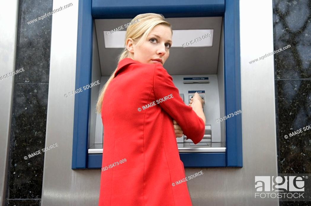 Stock Photo: Woman using cash machine.