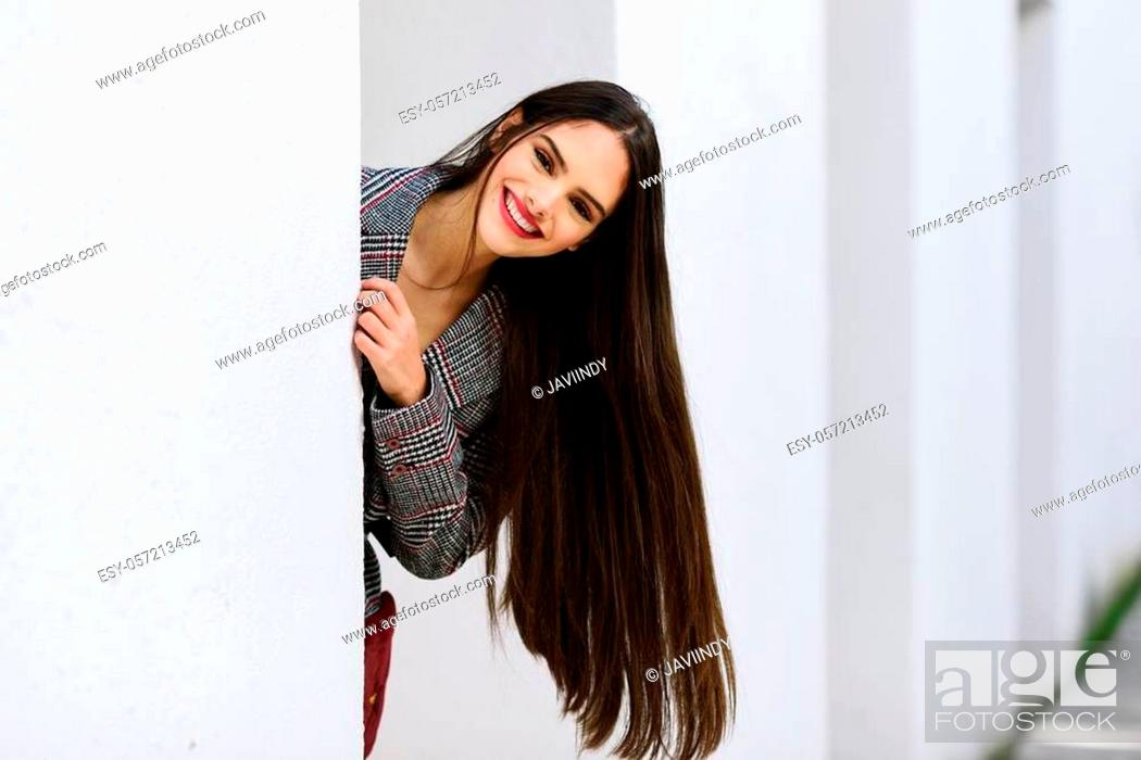 Stock Photo: Young beautiful girl with very long hair smiling at camera wearing winter coat and cap outdoors. Lifestyle and fashion concept.