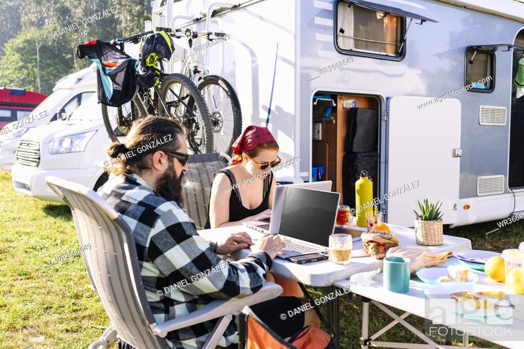 Stock Photo: Couple sitting next to camper using laptops on table.