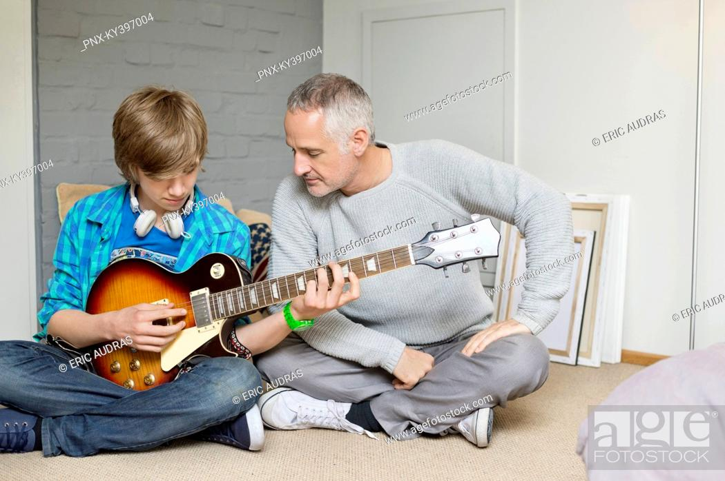 Stock Photo: Teenage boy learning guitar with his father at home.