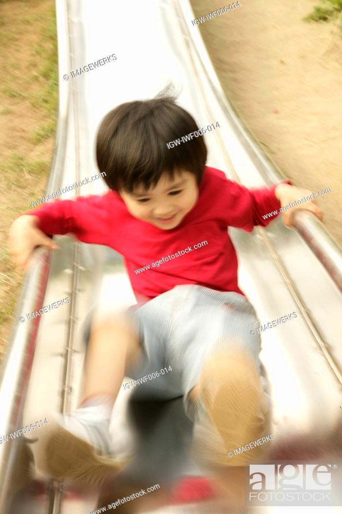 Stock Photo: A small boy enjoys himself sliding in the garden.