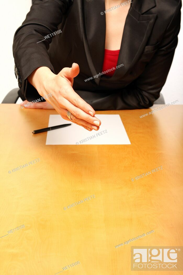 Imagen: View of a business-woman sitting at a desk greeting with a blank paper infront.