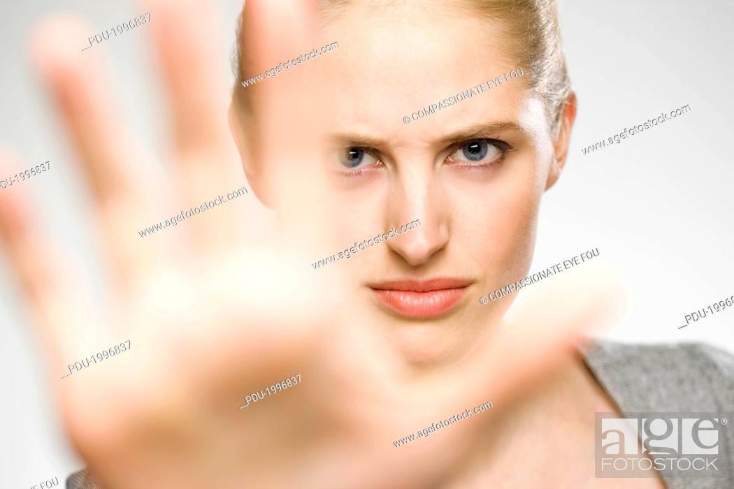 Stock Photo: Woman partially blocking her face with her hand.