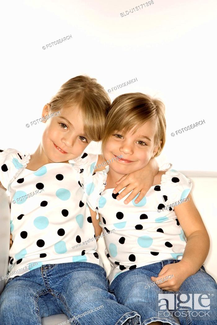 Stock Photo: Female children Caucasian twins sitting together on chair.