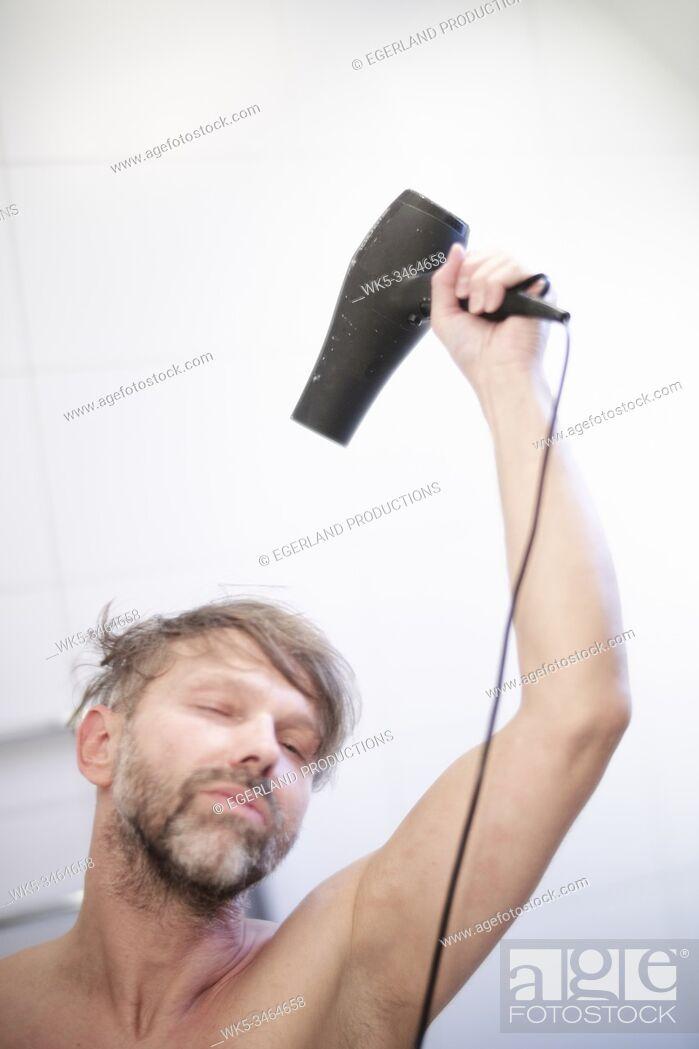 Stock Photo: Man using hair dryer.