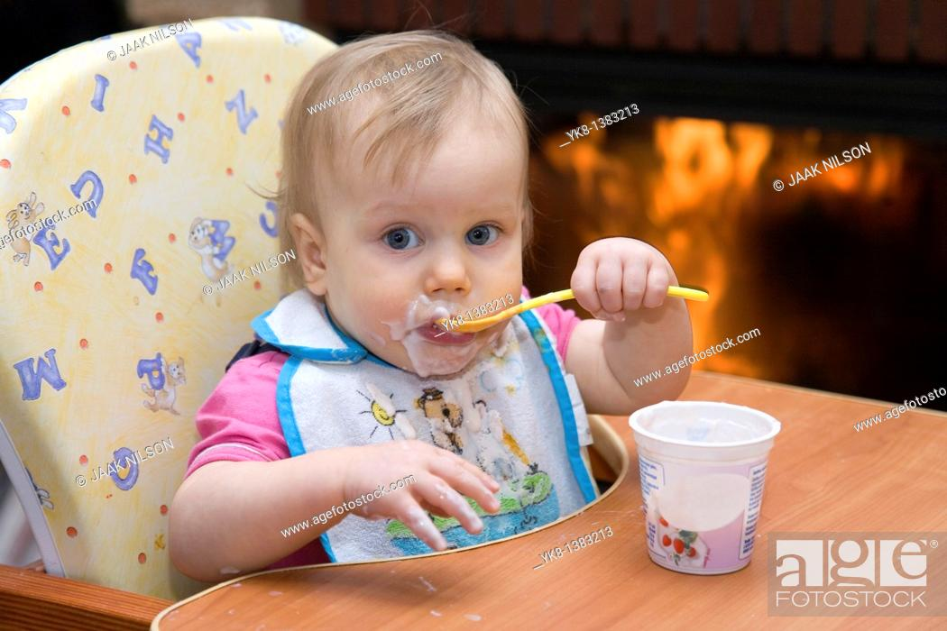 Stock Photo: One year old dirty baby girl in high chair eating yogurt using spoon.