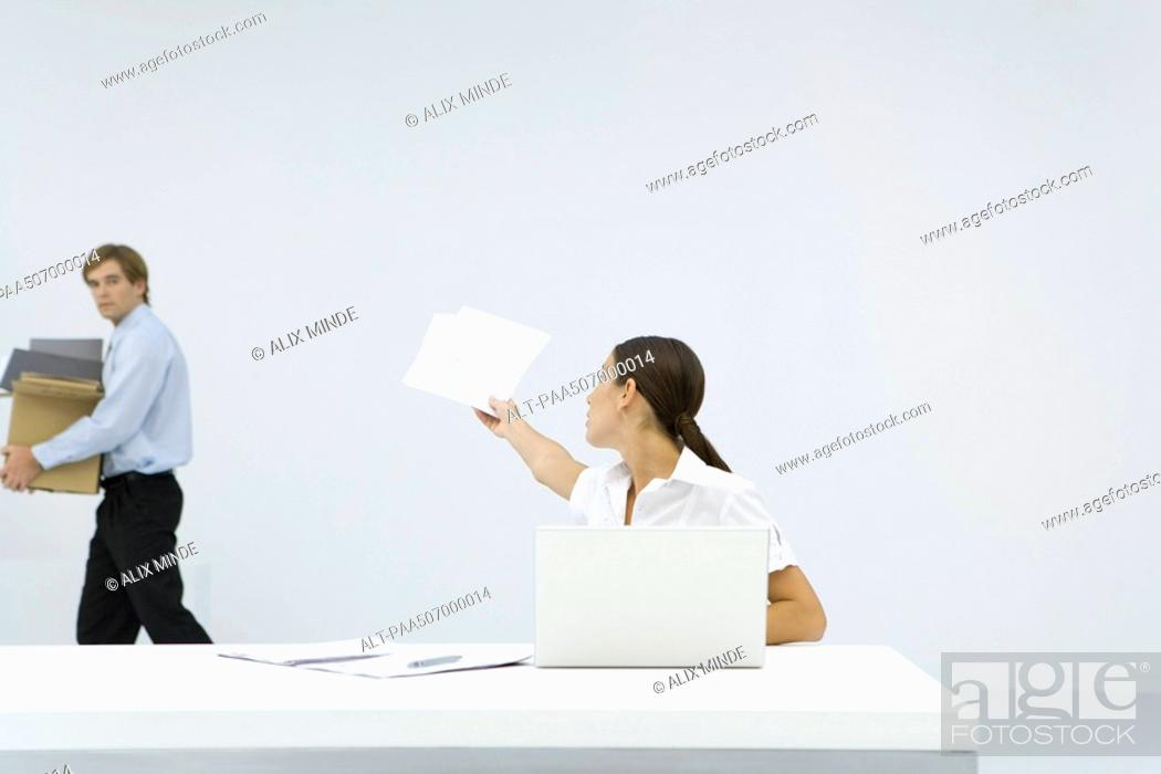 Stock Photo: Woman sitting at desk, reaching back to hand documents to man carrying a box.