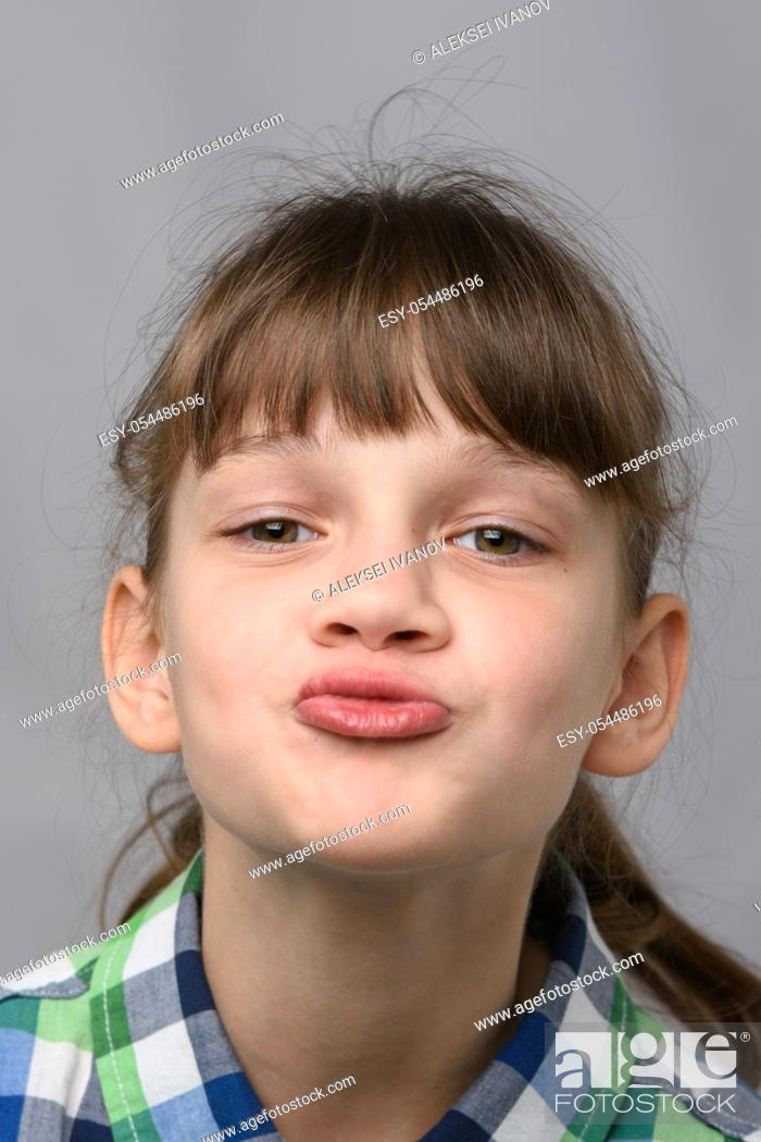 Stock Photo: Portrait of a ten-year-old girl showing a kiss, European appearance, close-up.