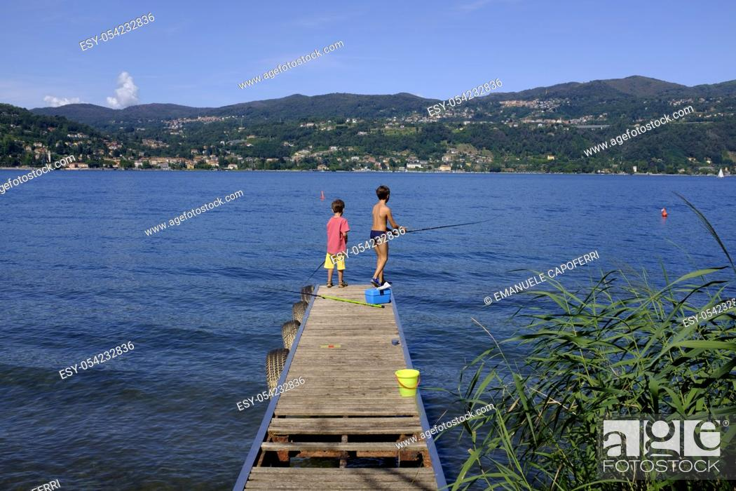 Stock Photo: Children fishing on the pier, Lake Maggiore, Ranco, Lombardy, Italy.